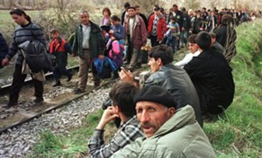 Kosovo refugees watch the stream of thousands of refugees arrive over the railroad tracks in Blace, Macedonia, on the border crossing with Kosovo on April 1, 1999.