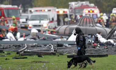"A responder using a dog patrols the grounds following a simulated radioactive ""dirty bomb"" attack Tuesday, Oct. 16, 2007, in Portland, Oregon."