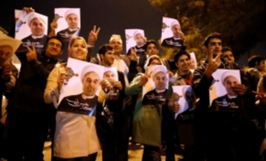 Iranians hold posters of President Hassan Rouhani as they welcome Iranian nuclear negotiators upon their arrival from Geneva at the Mehrabad airport in Tehran, Iran, Sunday, Nov. 24, 2013.
