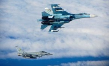 A Russian SU-27 Flanker aircraft banks away with a RAF Typhoon in the background. RAF Typhoons were scrambled on Tuesday 17 June 2014 to intercept multiple Russian aircraft as part of NATO's ongoing mission to police Baltic airspace.