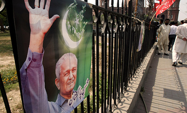 A poster on a fence in Lahore, Pakistan shows Pakistani nuclear scientist A.Q. Khan, glorified by many of his countrymen but reviled by Western governments.