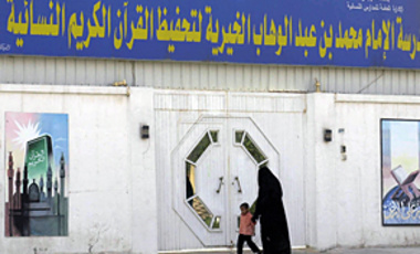 A Saudi woman and her son walk past the Imam Muhammad ibn Abdel-Wahhab Philanthropic School for Women's Quranic Studies in Riyadh, Saudi Arabia, March 21, 2003.