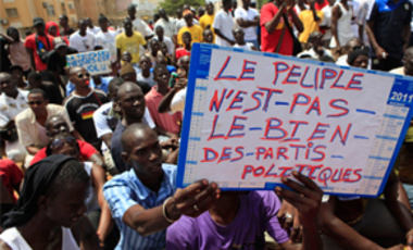 A protester holds a sign reading 'The people are not the property of the political parties,' during an opposition protest rally, in Dakar, Senegal,  July 23, 2011.