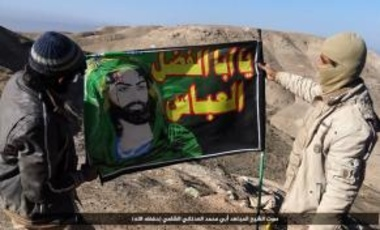 Islamic State fighters with flag captured from an Iraqi Shi'ite militia