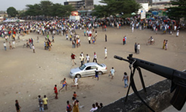 A sniper stands guard over a public square ahead of the arrival of Charles Ble Goude, a youth leader recently named to Laurent Gbagbo's cabinet who is staging rallies in support of the incumbent president, in Abidjan, Ivory Coast, Jan. 5, 2011.