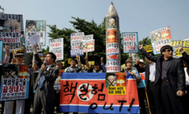 South Korean protesters holding defaced photos of North Korean leader Kim Jong Il shout anti-North slogans during a rally against North Korea's nuclear test in Seoul, South Korea, Monday, May 25, 2009.