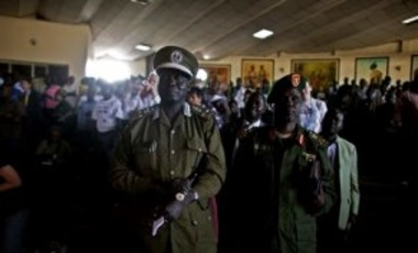 Two members of the South Sudan People's Liberation Army listen to an address by former South African President Thabo Mbeki, unseen, as he speaks to a group of southern Sudanese in the capital city of Juba, Jan. 7, 2011.