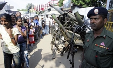 Sri Lankans look at artillery pieces captured from Tamil Tigers by the security forces at an exhibition in Colombo, Sri Lanka, Monday, Feb. 9, 2009.