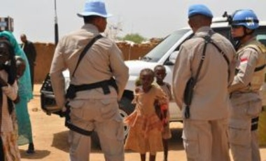 UN peacekeepers look on as curious children approach, 11 September 2009