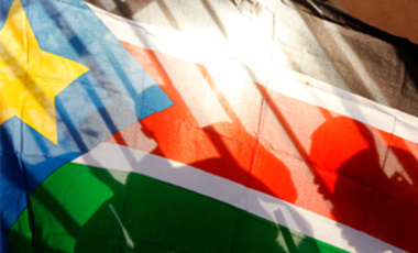 Southern Sudanese people are seen through a Southern Sudanese flag lining up to vote in Juba, Southern Sudan, Jan. 9, 2011. About 4 million Southern Sudanese voters began casting their ballots on Jan. 9 in a weeklong referendum on independence.