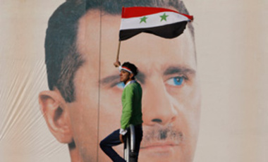 A pro-Syrian regime protester waves a national flag as he stands in front of huge portrait of Syrian President Bashar Assad during a protest against the Arabs and European sanctions, in Damascus, Syria, on Friday Dec. 2, 2011.