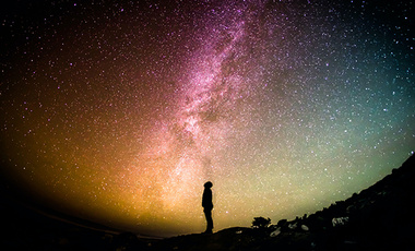 Silhouette of a person looking up at the Milky Way.