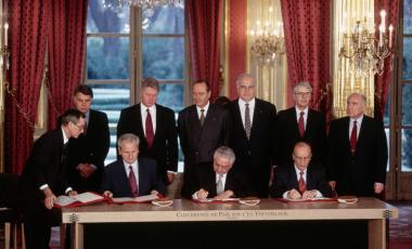 Leaders of six other nations look on as the presidents of Serbia, Croatia and Bosnia sign the Dayton Accords at the Elysee Palace in France.
