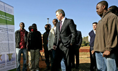 British Prime Minister Tony Blair listens to a student explaining the biofuel crops and research carried out at an experimental farm at Pretoria University in Pretoria, South Africa, June 1, 2007.