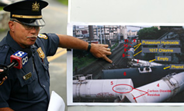 Derry Township Police Chief William D. Smith uses a photo during a news conference, July 6, 2006, to explain the contents of several chemical tanker cars that derailed near Hershey, Pa. 14 families and several businesses were evacuated.