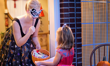 A woman hands out candy to a trick or treater.