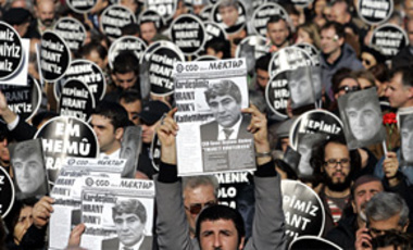 "Marchers hold placards that read: ""We are all Armenians"" & leaflets with the photo of slain ethnic Armenian journalist Hrant Dink in Istanbul, 23 Jan 2007. More than 100,000 marched in the funeral procession for Dink who had angered Turkish nationalists."
