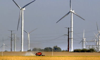 A combine harvests a field beneath Horizon Wind Energy's Twin Groves Wind Farm, Oct. 5, 2010 in Bloomington,IL.