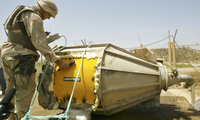 A U.S. soldier checks the radiation level of a canister found in Tuwaitha, 31 miles south of Baghdad. June 24, 2003.