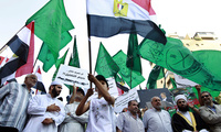 Members of Lebanon's Islamic Group, the country's branch of the Muslim Brotherhood, wave their party and Egyptian flags during a demonstration in front of the Egyptian embassy, in Beirut, Lebanon, Friday, July 12, 2013