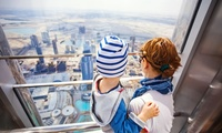 A mother holds her young child overlooking Dubai from the observation deck of the Burj Khalifa.
