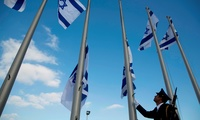 A member of the Knesset guard lowers the Israeli flags to half-staff in preparations to display the coffin of former Israeli President Shimon Peres at the Knesset, Israel's Parliament, in Jerusalem, Wednesday, Sept. 28, 2016.