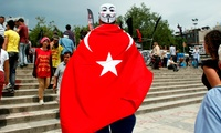 Giulio Giacomazzi 34, a tourist from Brazil wearing a Turkish flag and a mask enters Gezi Park, near Taksim square in Istanbul, Friday, June 7, 2013.