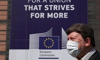 A man wearing a face mask walks past the European Commission headquarters in Brussels, Belgium on April 9, 2020