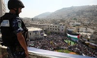 A Palestinian police officer watches a rally in support of the Palestinian bid for statehood recognition in the United Nations, in the West Bank city of Nablus.