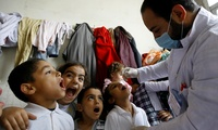 Syrian displaced children line up to receive vaccination against polio at one of the Syrian refugee camps in the southern port city of Sidon, Lebanon, Thursday, Nov. 7, 2013, following an outbreak of the crippling and highly communicable disease in neighboring Syria.