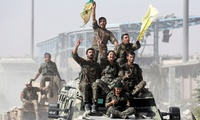 Syrian Democratic Forces (SDF) fighters ride atop of military vehicles as they celebrate victory in Raqqa, Syria.