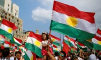 A man holds a girl waving a Kurdish flag as they gather to support next week's referendum in Iraq, at Martyrs Square in Downtown Beirut, Lebanon, Sunday, Sept. 17, 2017.