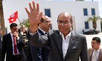 Tunisian former president Moncef Marzouki arrives to take part in an anti-extremism march, in Tunis, Sunday, March 29, 2015.