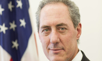 Ambassador Michael Froman stands in front of an American Flag