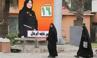 Women walk past an election campaign poster for candidate Mai Nayef al-Rahal of the Iraq coalition at Kahramana Square in Baghdad, Iraq,Tuesday April 1, 2014.