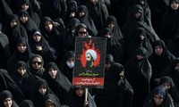 An Iranian woman holds up a poster showing Sheikh Nimr al-Nimr, a prominent opposition Saudi Shiite cleric who was executed by Saudi Arabia, in Tehran, Iran, Monday, Jan. 4, 2016.