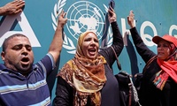 Palestinians demonstrate outside the UNRWA Gaza Headquarters against cuts and the possibility of delaying the school year due to severe deficit in the agency's budget, in Gaza City, Monday, Aug. 10, 2015.