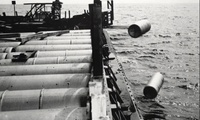 A forklift shovels one-ton containers of mustard gas over the side of a barge somewhere in the Atlantic Ocean in 1964. The Army dumped millions of pounds of chemical warfare agent over decades in this way.