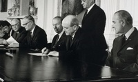 President Lyndon Johnson looking on as Secretary of State Dean Rusk prepares to sign the NPT, 1 July 1968.