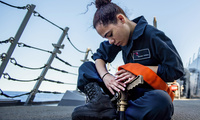 Photo of Navy Seaman Arionna Russell connecting a fire hose to a P-100 fire pump during maintenance aboard the USS Michael Murphy in the Pacific Ocean.