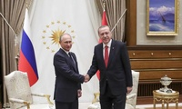 Turkey's President Recep Tayyip Erdogan, right, shakes hands with Russian President Vladimir Putin