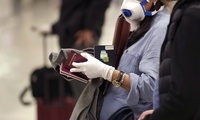 International travelers, some wearing protective masks and gloves, wait in line.