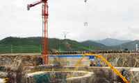 A crane carries a bucket containing concrete to the foundation of a reactor during the first concrete pouring for the Light Water Reactor Project in North Korea on August 7, 2002.