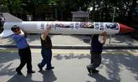 South Korean activists carry a mock North Korean missile during a rally denouncing the North's nuclear program in Seoul, South Korea, Thursday, June 25, 2009. (AP Photo/Lee Jin-man)