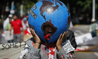 An anti-globalization demonstrator shouts slogans during a march against the North American Leaders summit in Guadalajara on Sunday August 9, 2009. (AP Photo/Eduardo Verdugo)