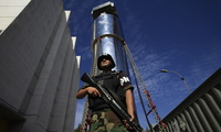 "A soldier guards a transport cask containing a transfer cylinder that holds highly enriched uranium at ""La Reina"" reactor in Santiago, Chile on February 18, 2010. (AP Photo/Jorge Saenz)"