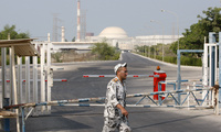 An Iranian security guard walks past a gate of the Bushehr nuclear power plant in Iran in 2010 (AP Photo/Vahid Salemi).