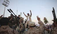 Revolutionary fighters, beside an anti-aircraft machine gun, center, demonstrate in favor of the National Transitional Council, NTC, at Tripoli's main square, Libya, Monday, Oct. 3, 2011.
