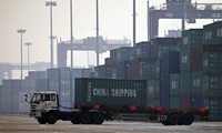 In this photo taken Feb. 28, 2012, a truck transports a container to be loaded onto a ship at a port in Tianjin, China (AP Photo/Alexander F. Yuan).