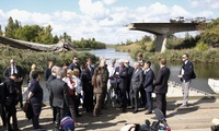 French Foreign Minister Jean-Marc Ayrault, third right front, and German Foreign Minister Frank-Walter Steinmeier, fourth right front, stand in front of a bridge that was destroyed by shelling during the battle for Slovyansk in summer 2014, in Seleznivka village, eastern Ukraine, Thursday, Sept. 15, 2016.